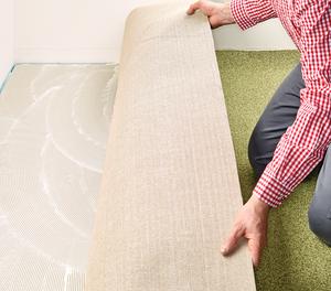 Den zurückgeschlagenen Teppich in das Klebstoffbett einlegen und mit einem geeigneten Werkzeug gut anreiben, besonders am Rand- und Nahtbereich. Diesen Vorgang nun auch mit der anderen Hälfte wiederholen.