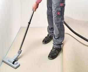 Den Teppich über die Breite bis zur Hälfte vorsichtig zurückschlagen und  den Untergrund sowie die Rückseite des Belages gründlich absaugen. Der Teppich darf beim Zurückschlagen nicht verrutschen ggf. den Teppich beschweren.